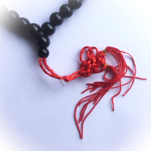 red tassel enbellishes the rosary