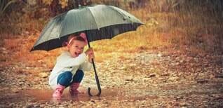 Faltkarte (7x14.5) Kind im Regen mit Regenschirm