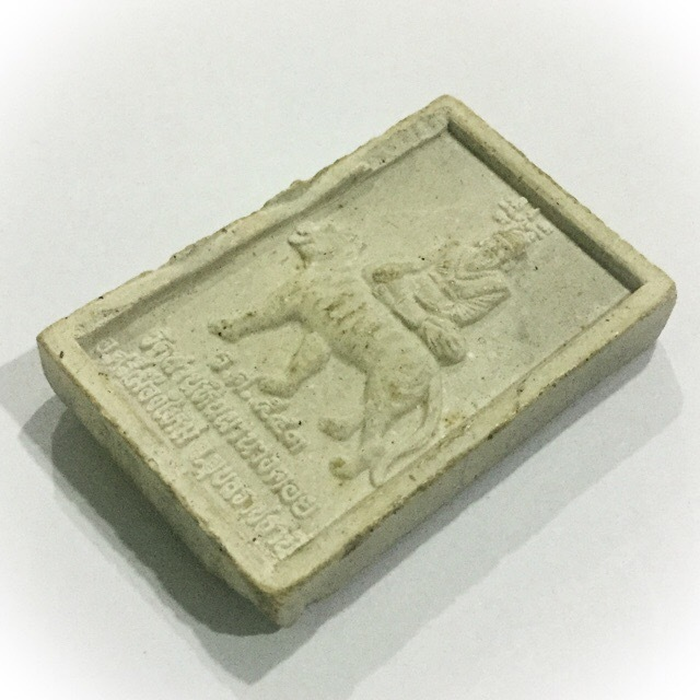 The rear face of the amulet features the Lersi Hermit God Por Gae riding on the back of a Tiger.