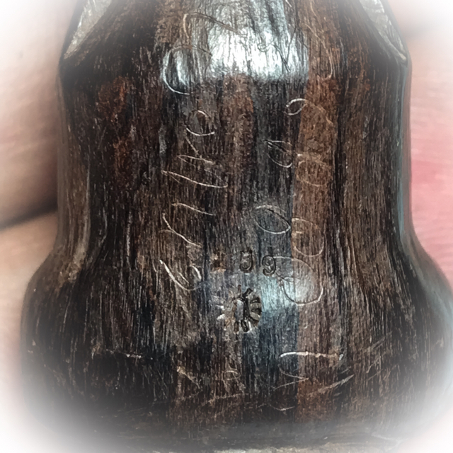 The limited series code number is embossed on the rear side of the amulet - spell inscriptions in Kher Sanskrit are visible on the surface of the sacred wood