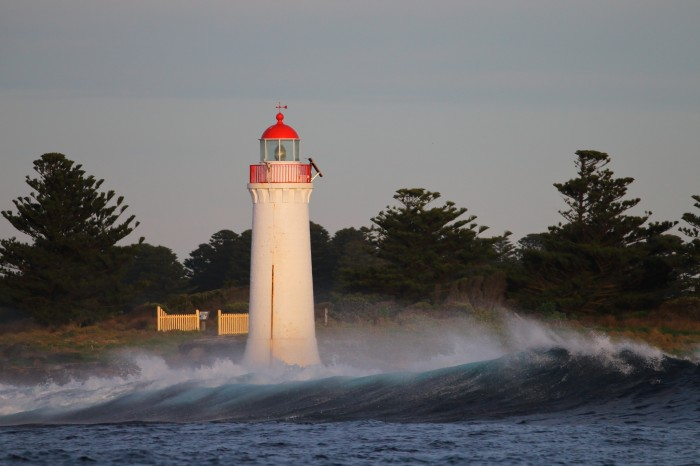 Lighthouse and wave in Port Fairy, Victoria; photo by Ed Dunens