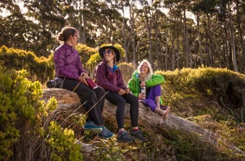 Three-Women-Hiking-in-KEEN-Versatrail-sitting-on-log