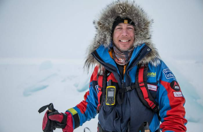 Eric Larsen smiling in full gear, arctic terrain in background