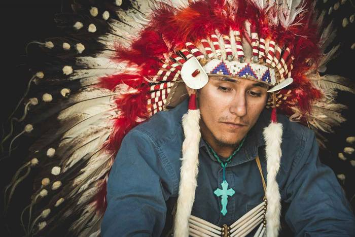 Young native man poses for a photo in his families 90 yr old war bonnet