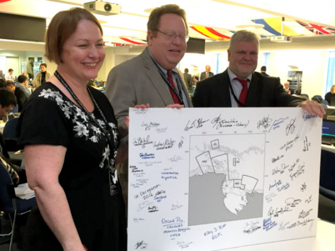 Jillian Dempster (left, New Zealand) and Evan Bloom (center, USA) with CCAMLR Chair Vasily Titushkin (right) show a signed map of the Ross Sea MPA