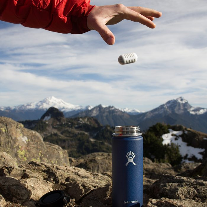 hand dropping a gopure filtration pod into hydro flask