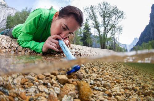 Woman Using LifeStraw Personal Water Filter in Stream