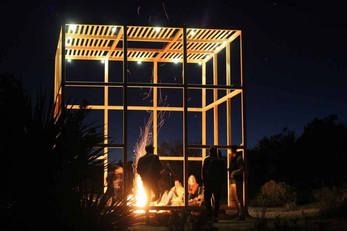 Participant-built structure at 'The Outpost,' campfire inside, Goal Zero lights above