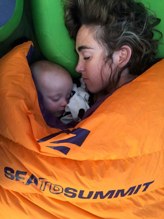 mom sleeping with young baby camping