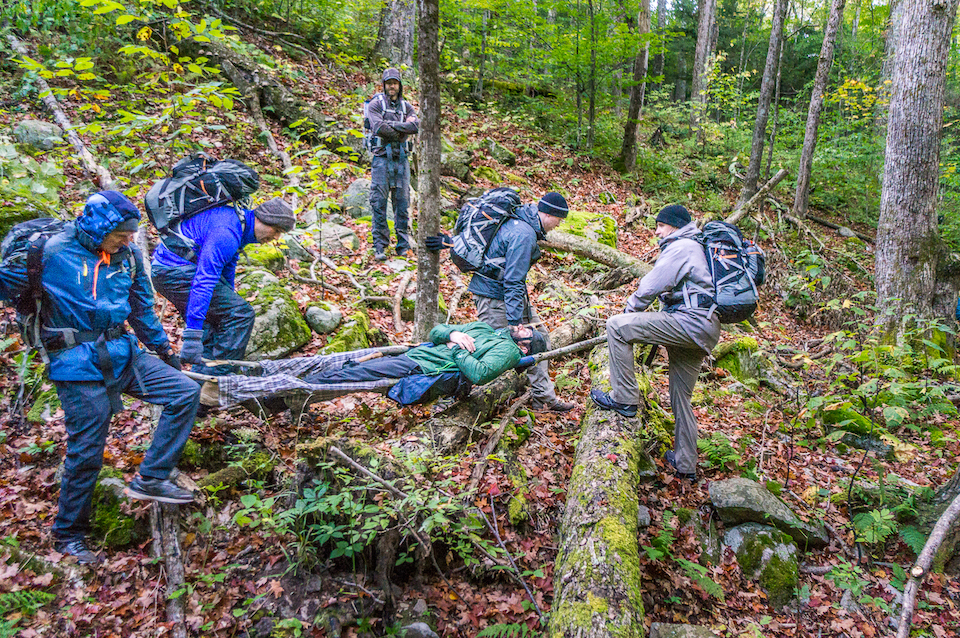 Carrying an injured hiker out of the woods at Bear Grylls Survival Academy