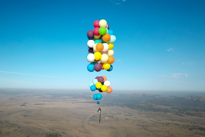 helium balloons lift chair and person