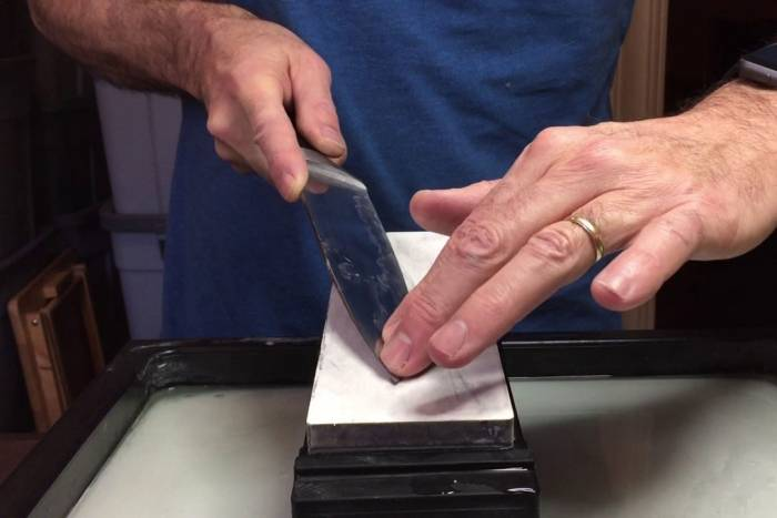 sharpening a knife on whetstone