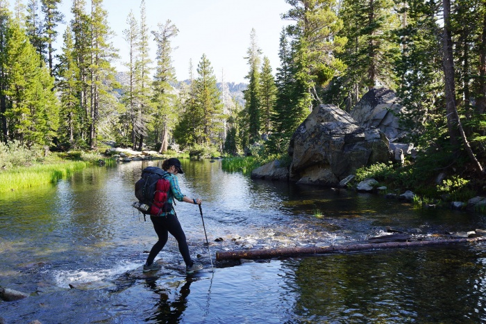 Female hiker crossing a creek