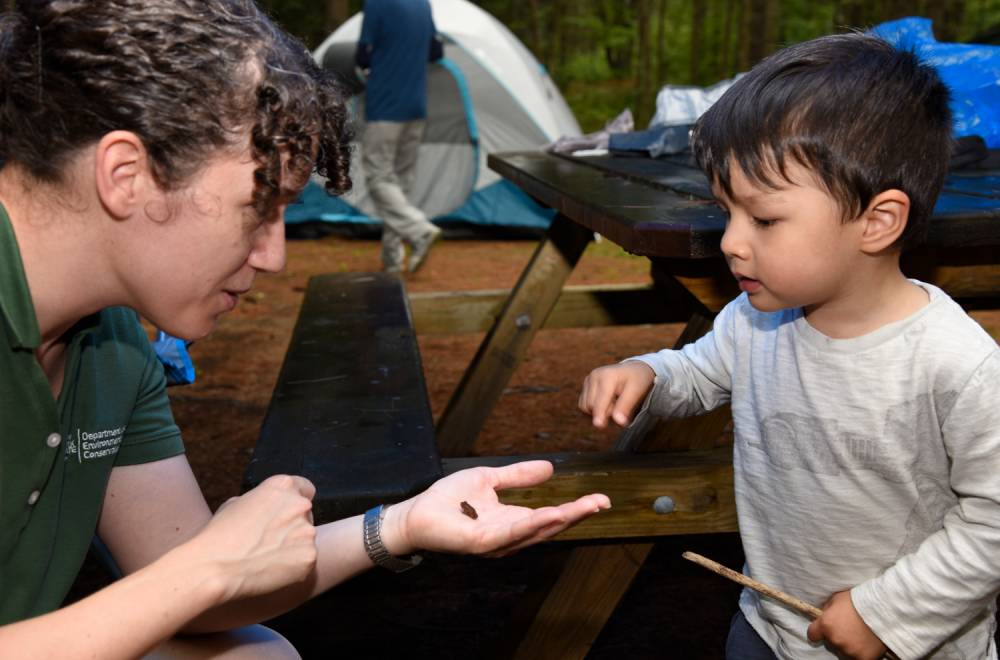Camp Ambassador teaches a young child about local wildlife