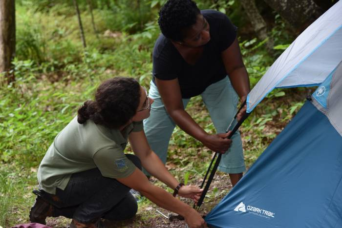 NY Camp Ambassador instructs a first-time camper how to set up a tent