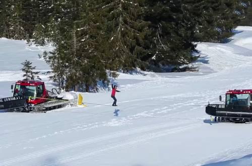 slackline between two snowcats