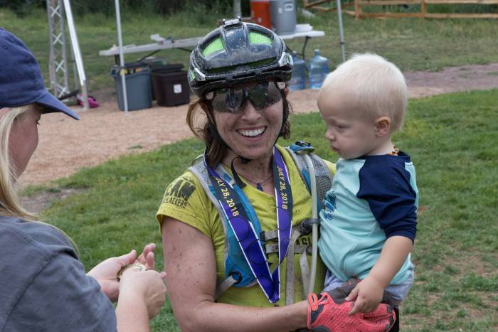 Chelsey Magness finished 3rd at the Telluride 100 MTB Race. She celebrates with son Max