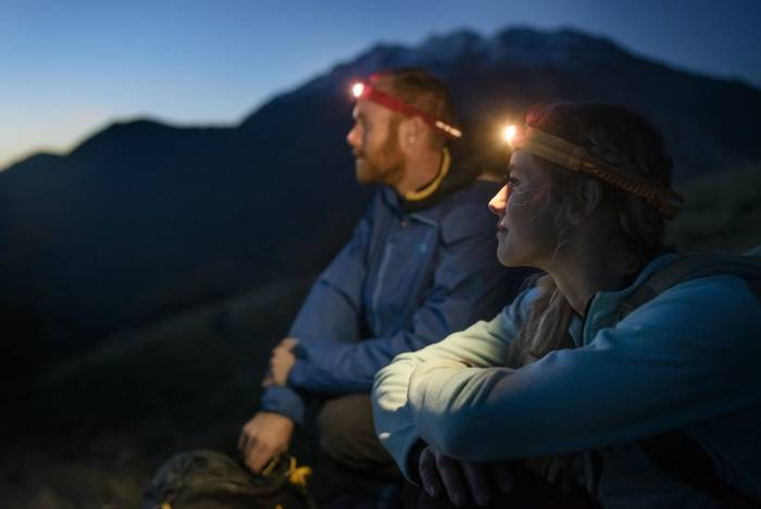 Two hikers using BioLite HeadLamp 330 at dusk, mountains in background