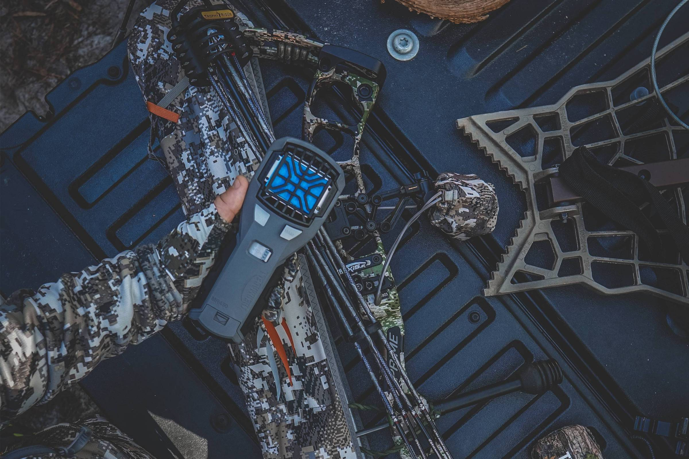 thermacell mr450 held in a hand over a truck bed full of hunting equipment