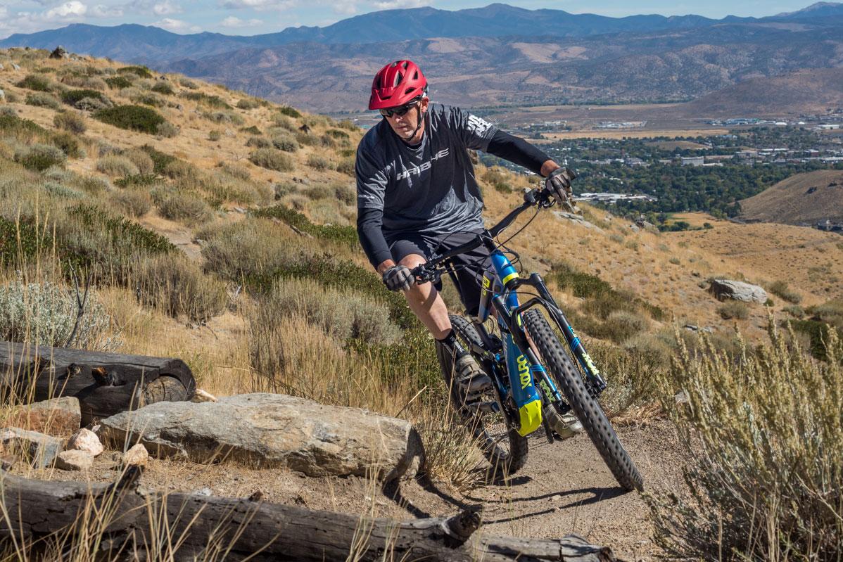 Man on the HaiBike XDUR0 AllMtn 9.0 mountain bike, mountains in background