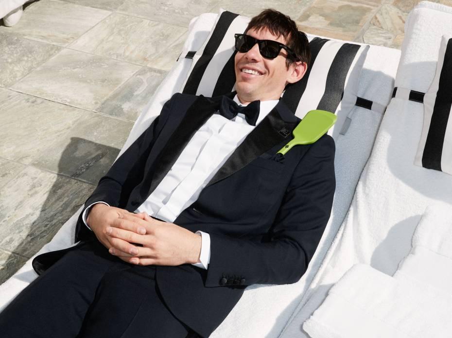 Alex Honnold lounging beach chair in a tux