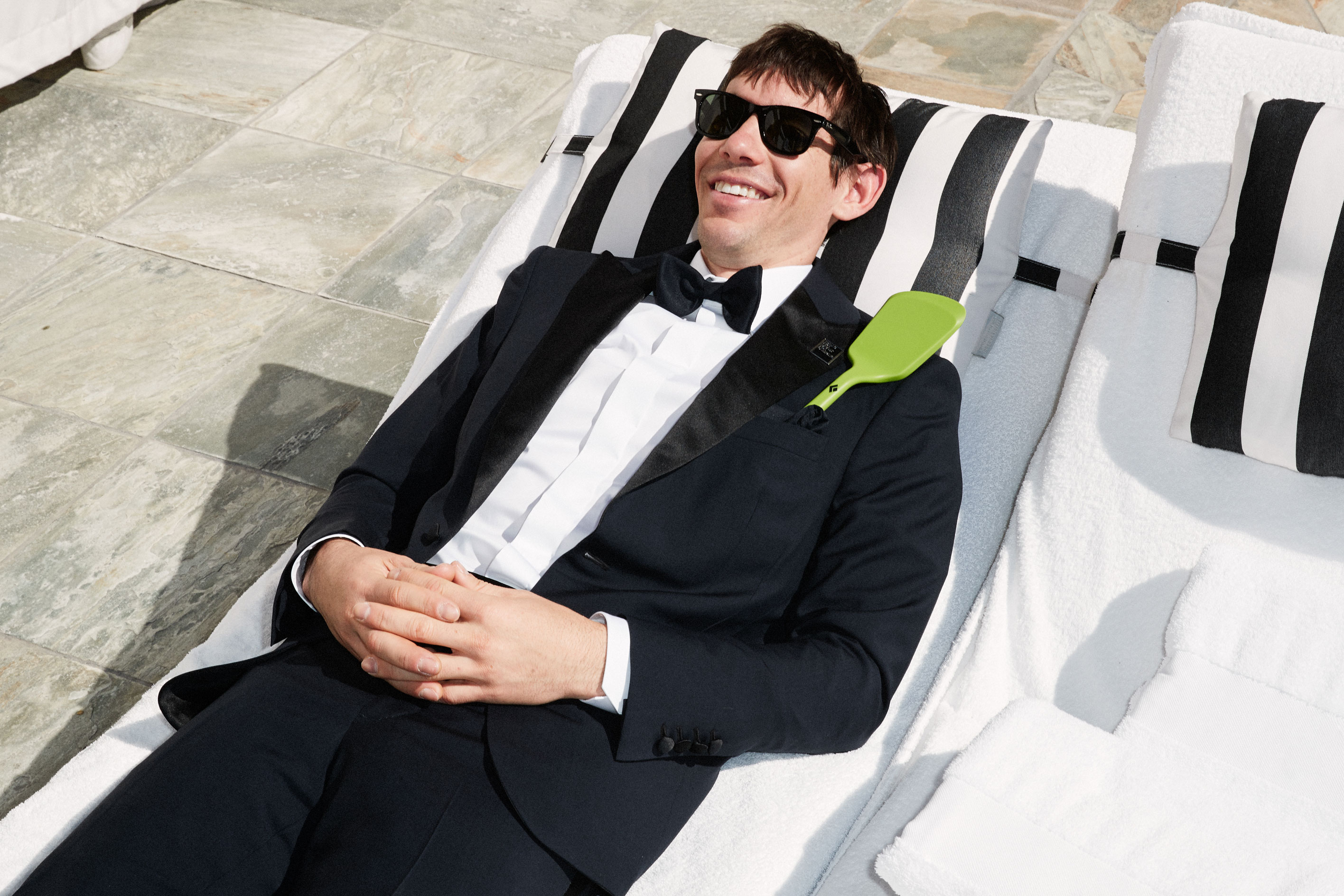 Alex Honnold lounging beach chair in a tux
