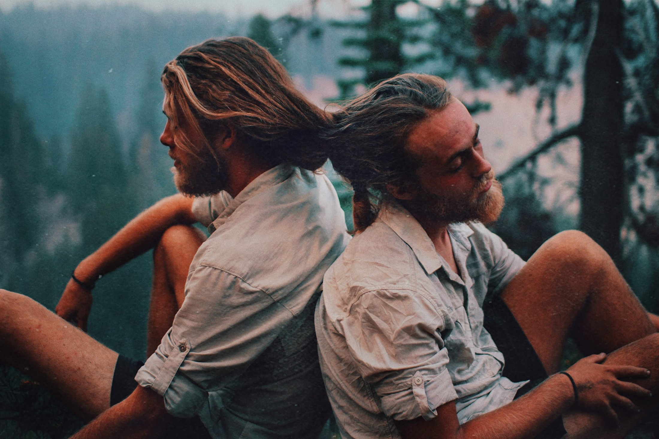 Two men sitting on the PCT with their hair tied together