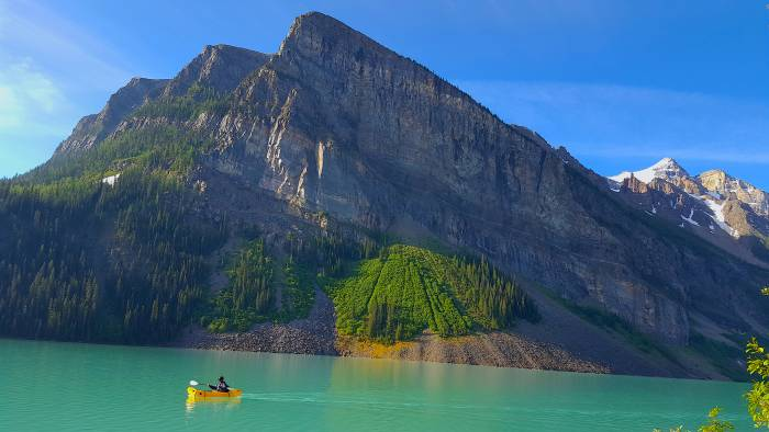 Paddler on turquoise water, mountains in background