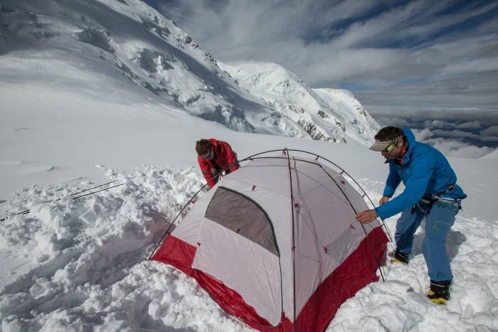 Two people setting up a tent on a snowy mountainside