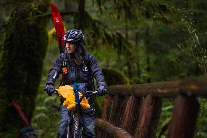 Bikepacker on bike in full gear, including a packraft and paddle, crossing a bridge