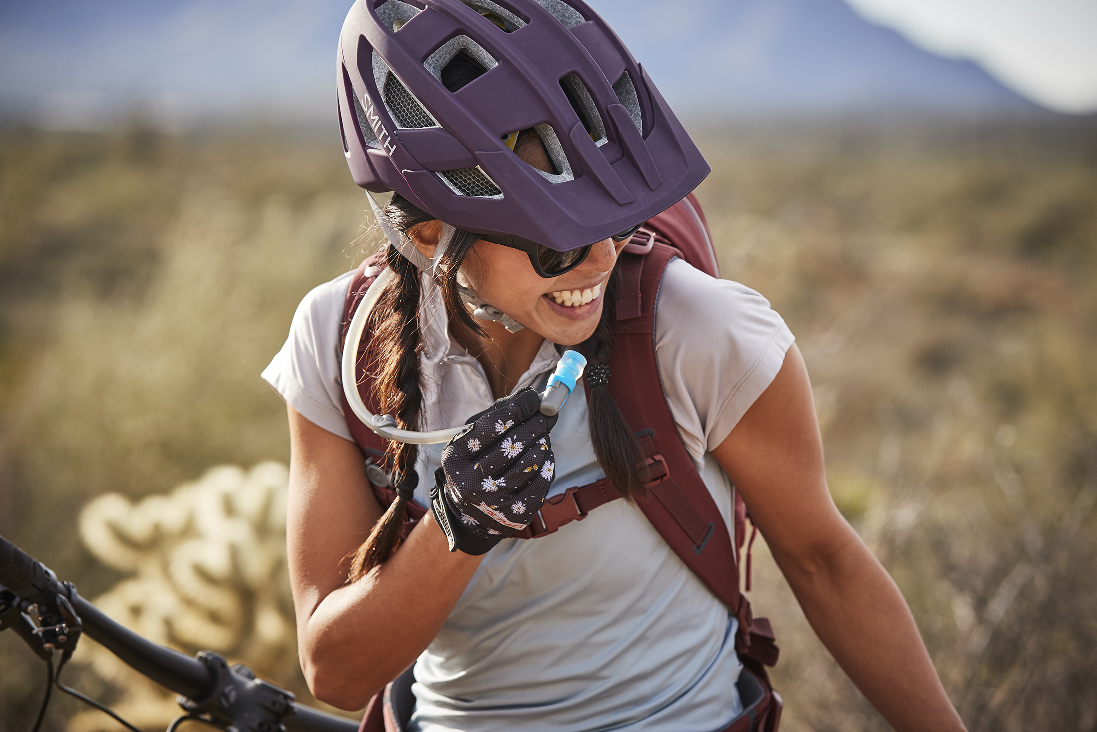 Closeup of mountain biker smiling, drinking from Hydro Flask Journey pack