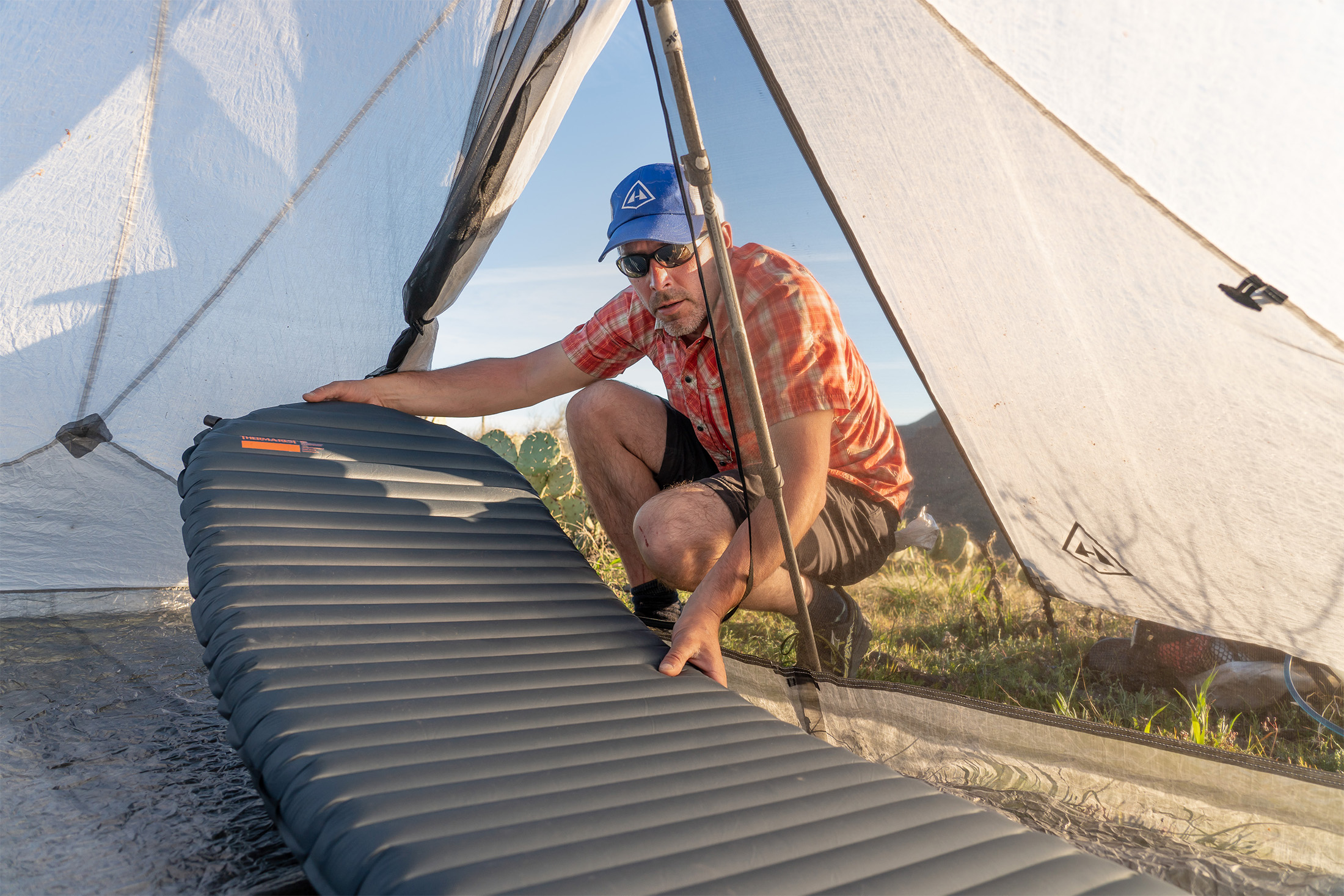 Man placing sleeping pad inside Hyperlite Mountain Gear Dirigo 2 tent