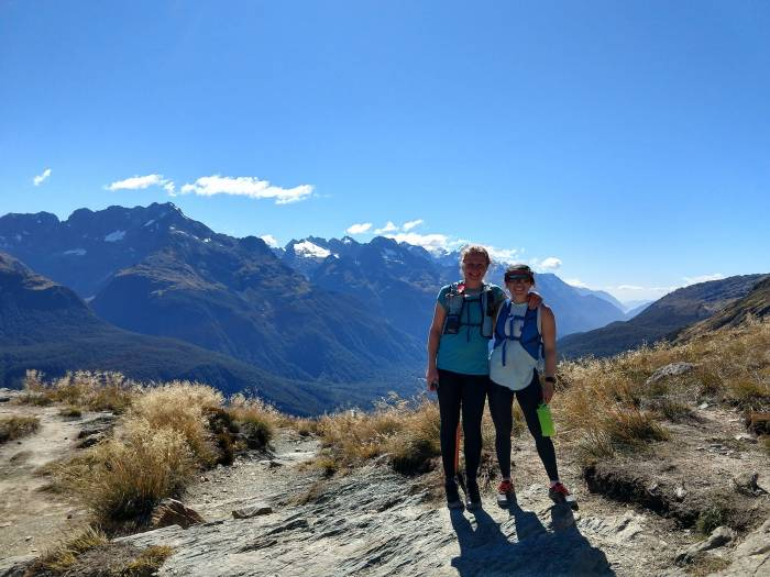 Two runners on the Routeburn Track, mountains in background