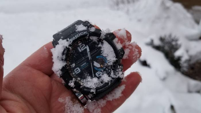 Casio Mudmaster watch in author's hand, covered in snow