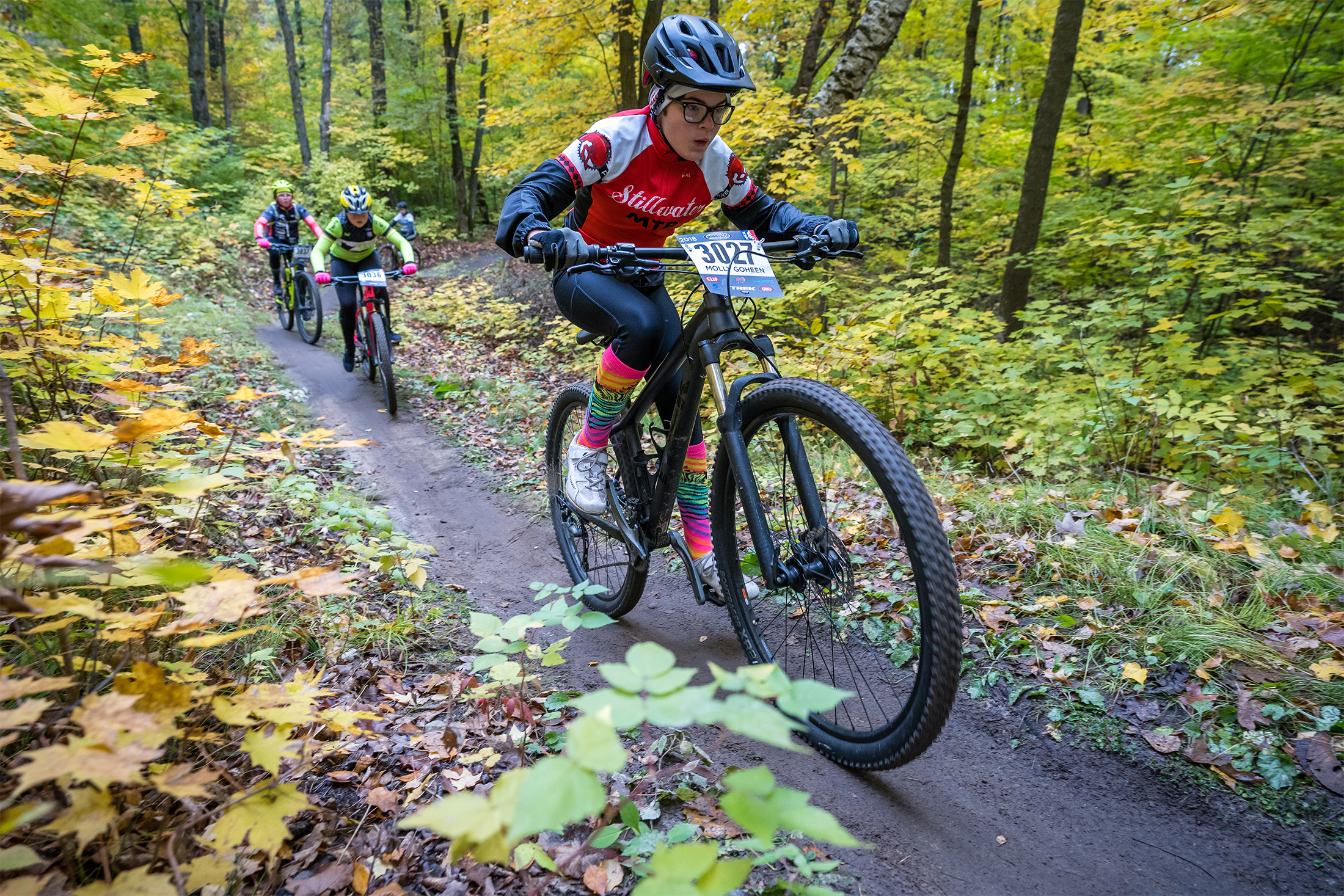 Four high-school cyclists racing each other on a woodland trail
