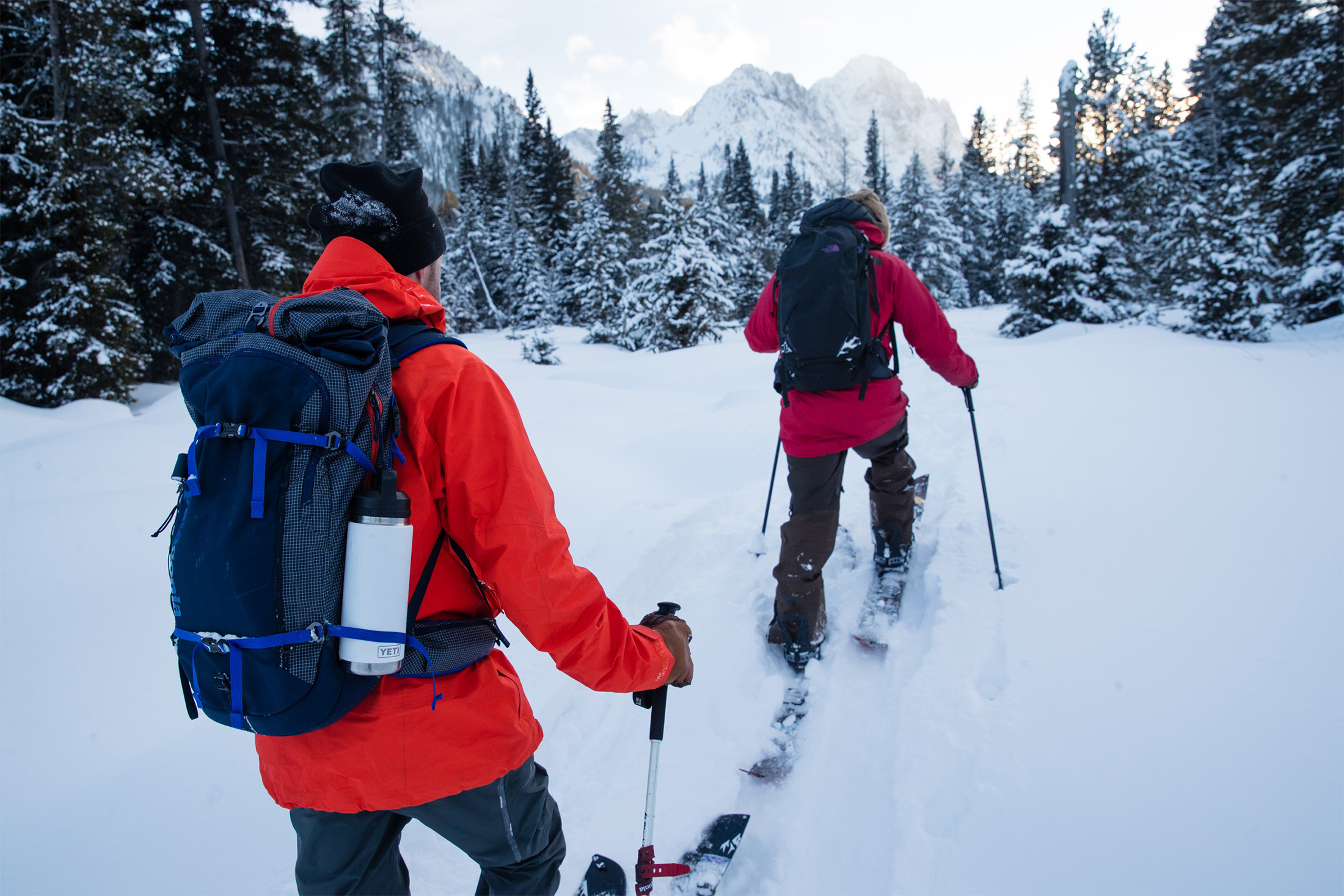 Two backcountry skiers, one carrying a YETI Rambler