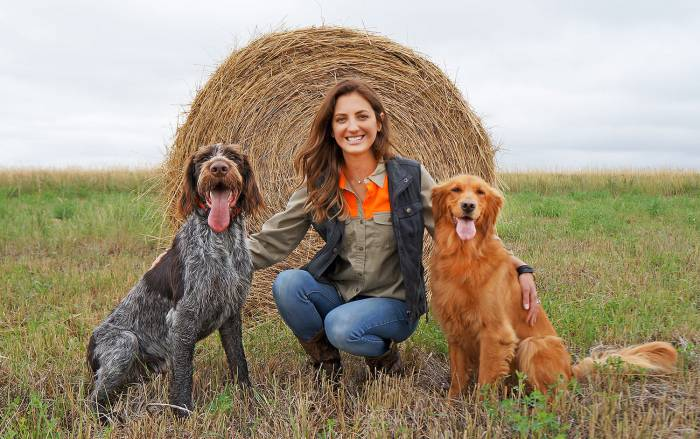 Danielle Prewett with two dogs in front of a hay bale