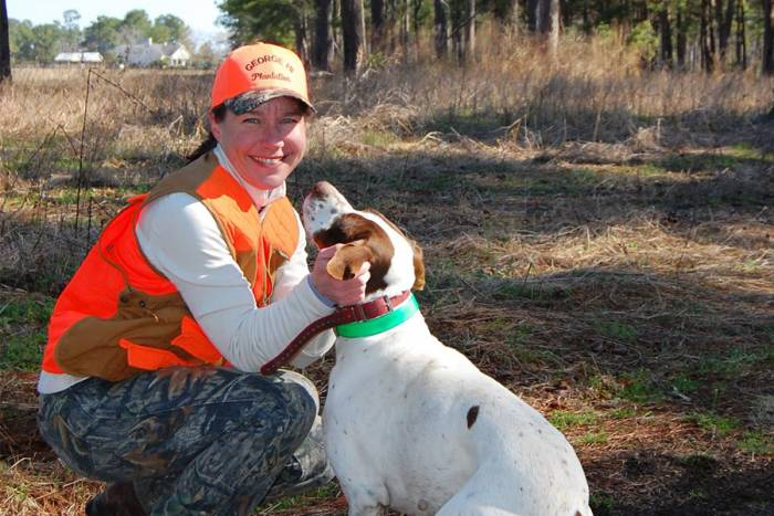 Katie McKalip in camo and orange, petting a dog