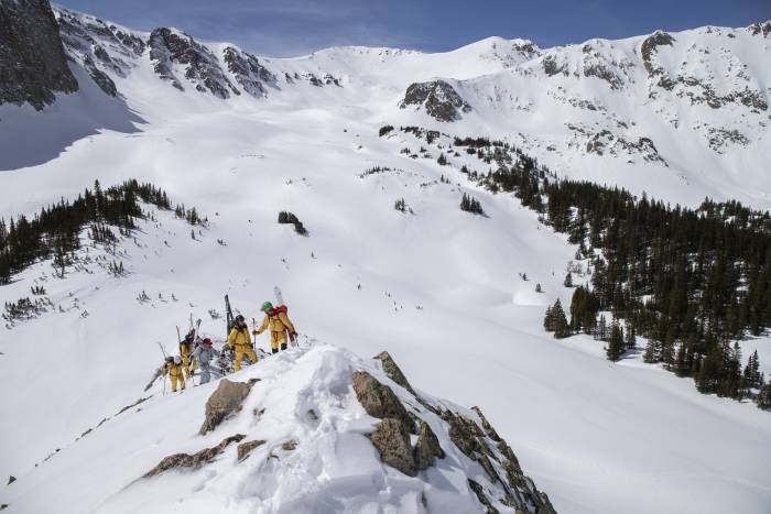 Skiers wearing The North Face FUTURELIGHT, summiting a peak