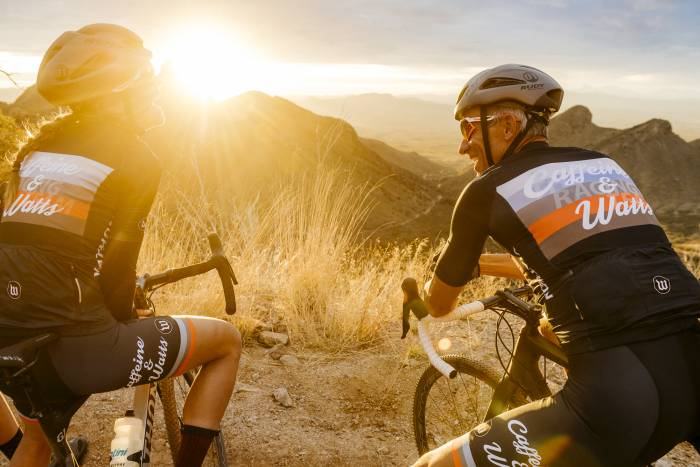 Two cyclists on bikes up close, sunset in background