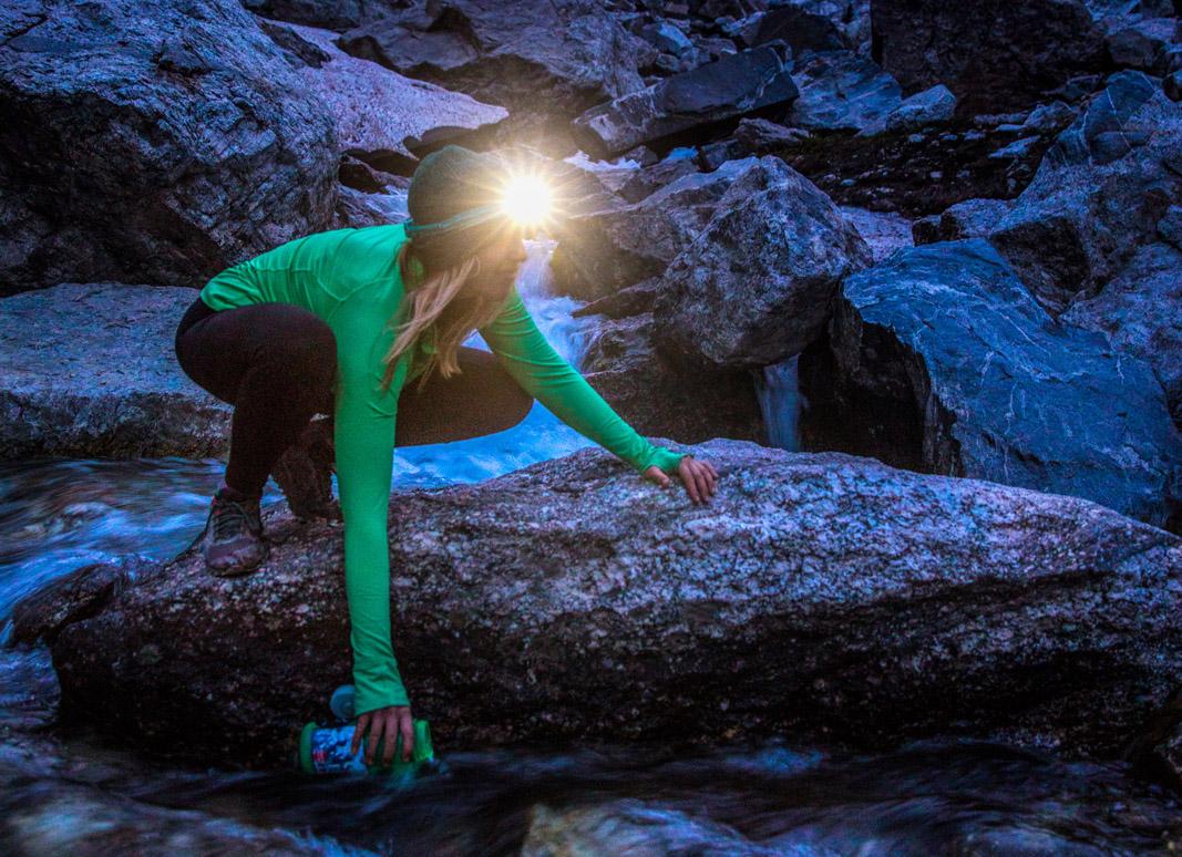 Woman-in-BioLite-HeadLamp-Filling-Water-at-Stream