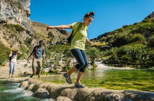 Person Hiking in Merrell Footwear Across a River