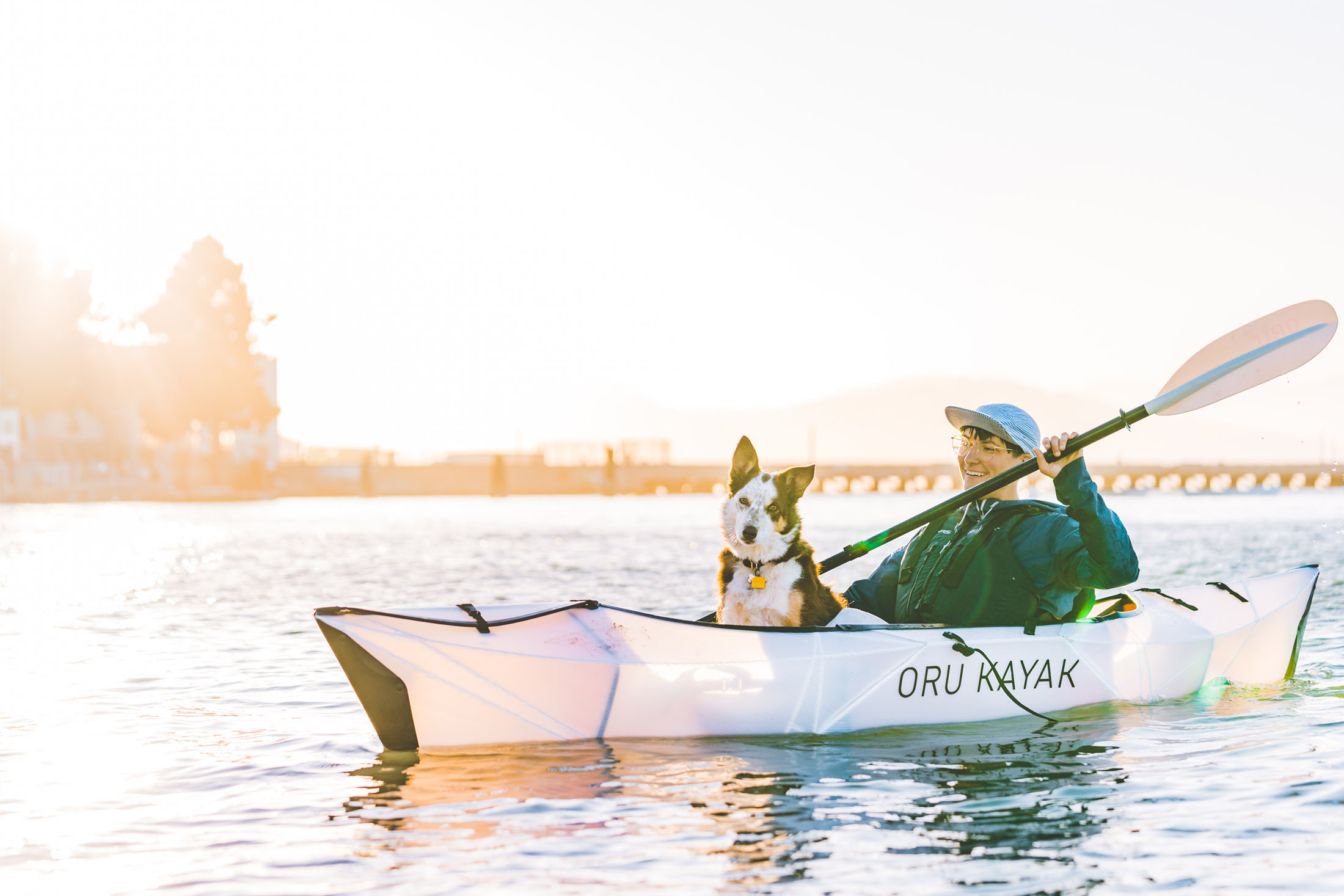 Person Paddling in Oru Kayak with dog