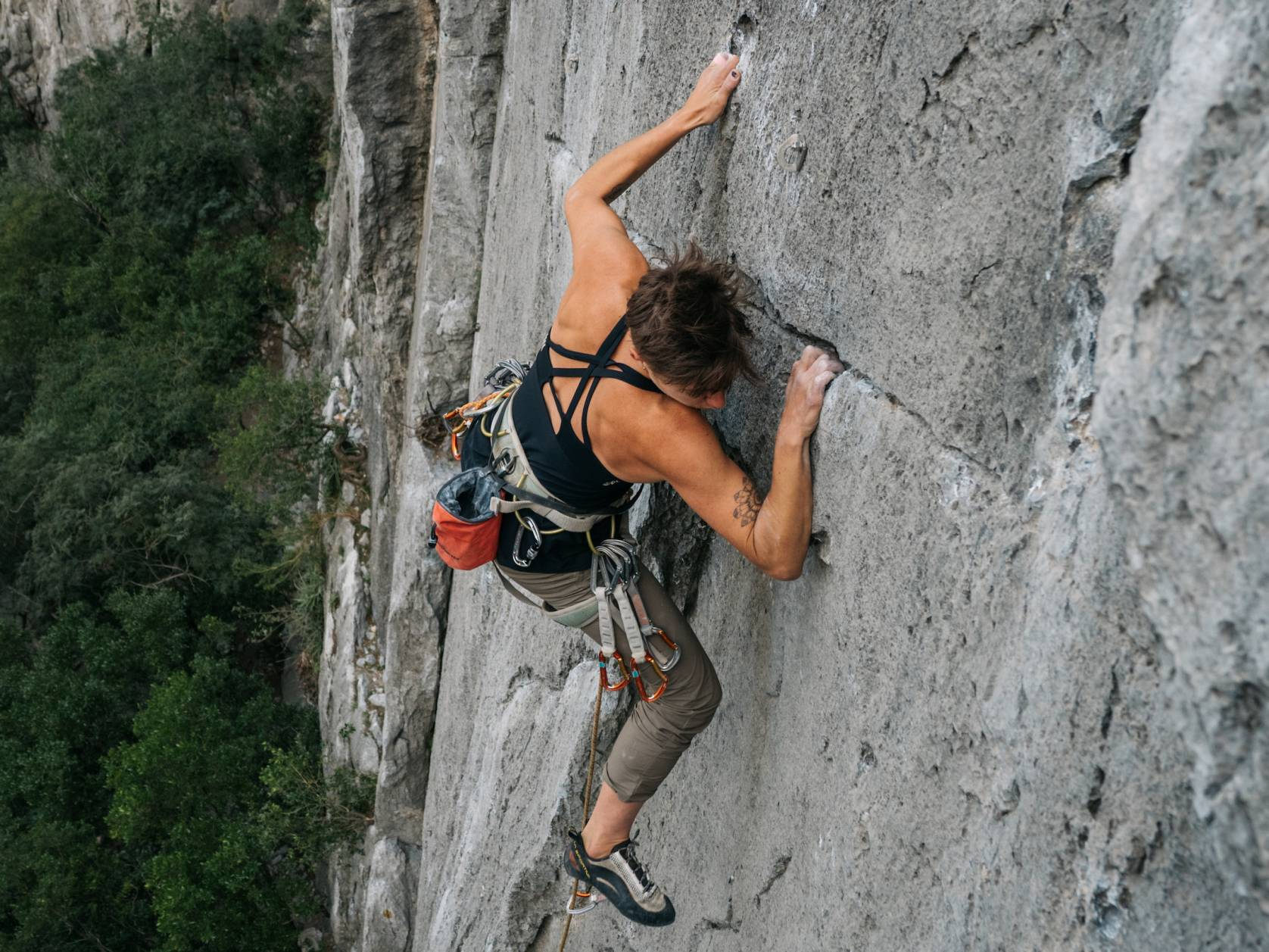 Female with short hair climbing in HoldBreaker Sports Bra