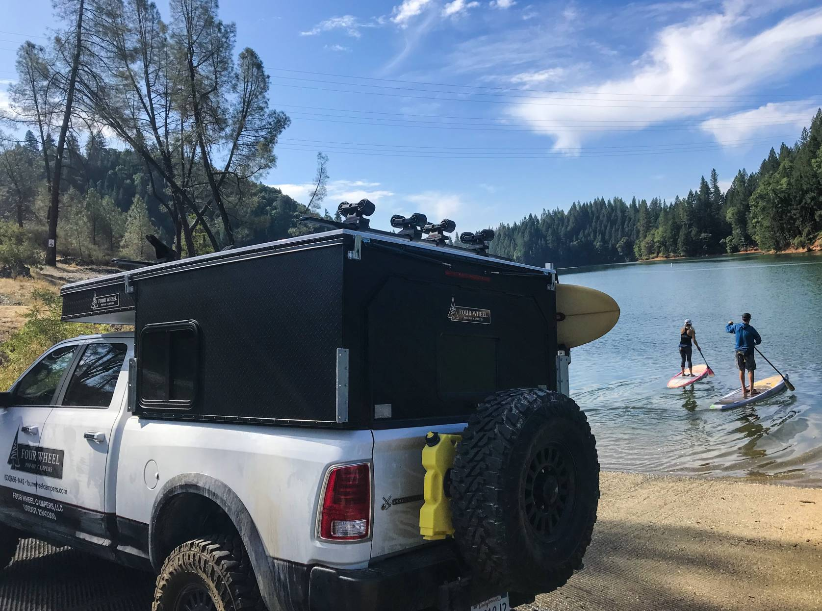 truck parked in front of lake with stand-up paddleboarders in background