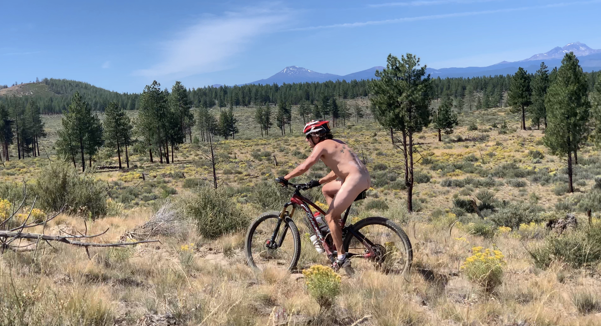 Man rides a mountain bike naked