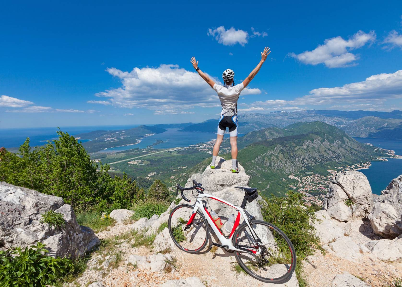 man standing on mountain top with arms outstretched with his bike nearby