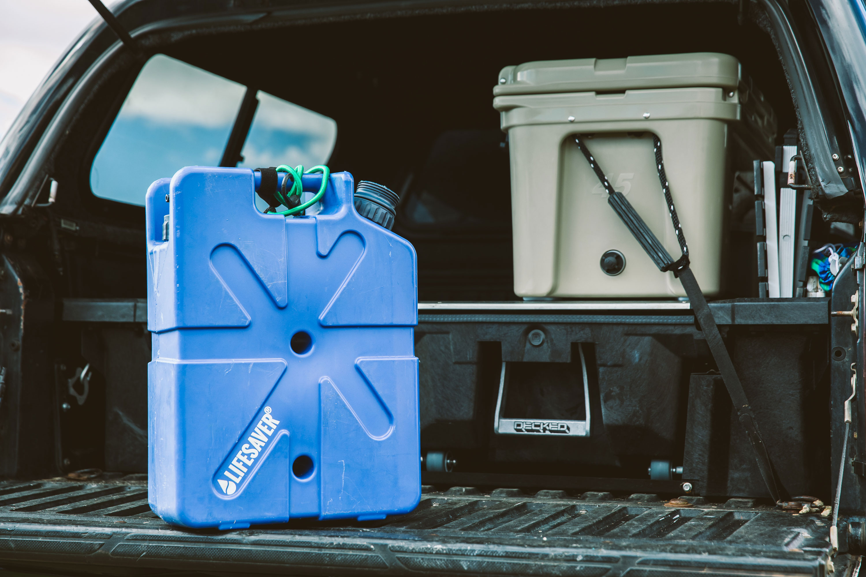 A blue LifeSaver Jerrycan resting on truckbed