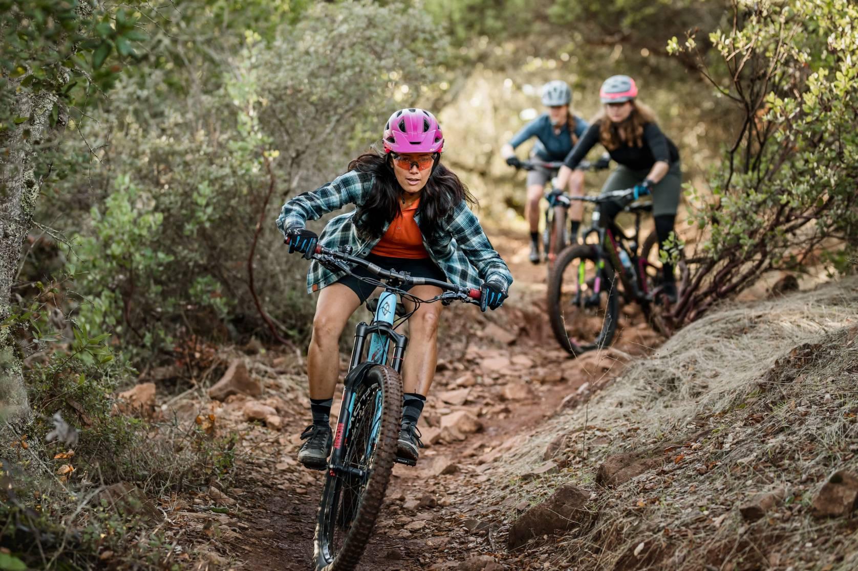 group of women mountain biking down trail in fall