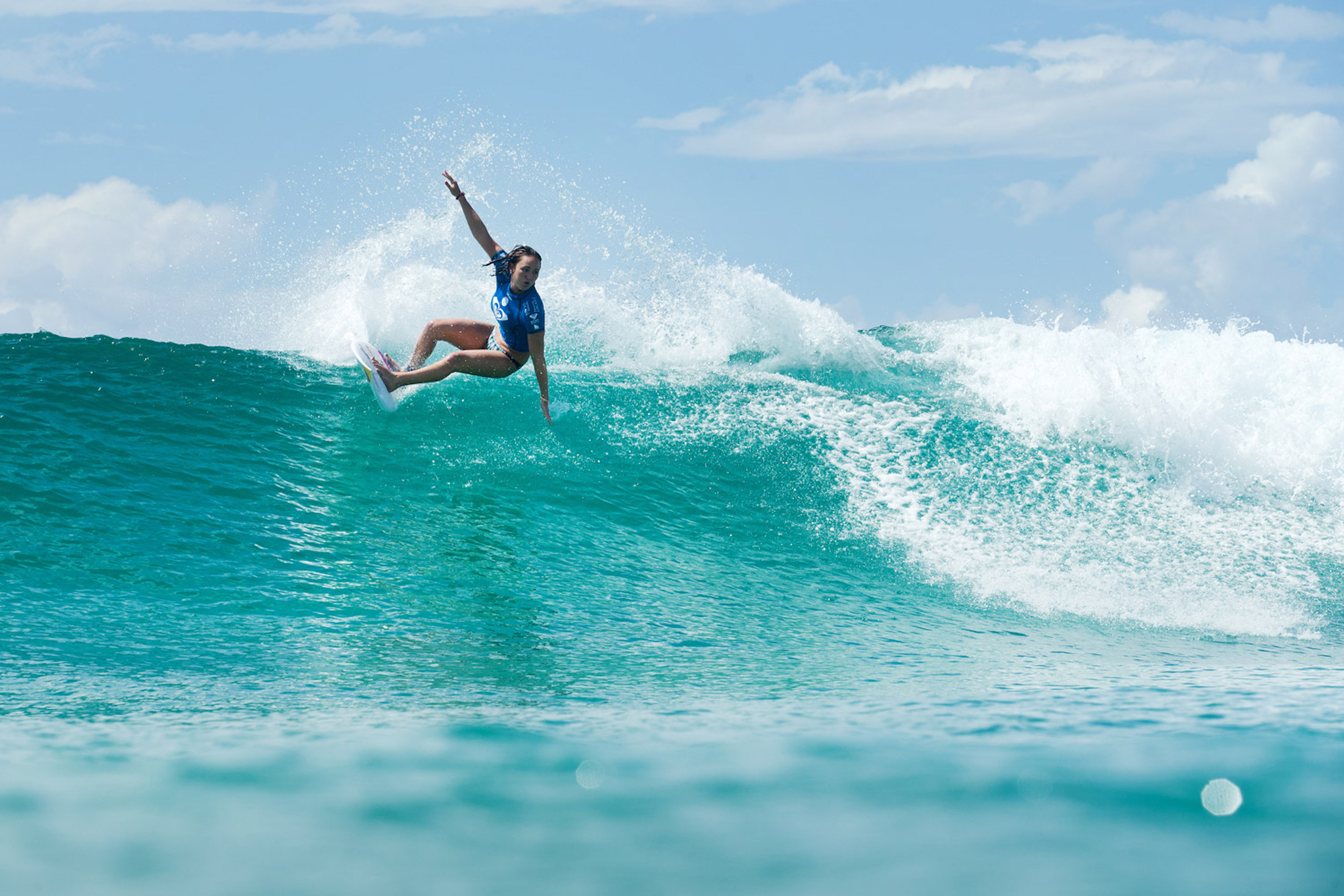 Carissa Moore surfing wave on a sunny day